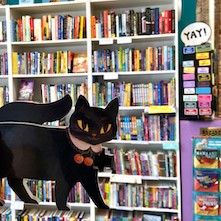 A display of books plus a cartoon black cat at Second Star to the Right Books