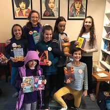 Young book club members holding books at Brain Lair Books