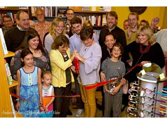 A crowd cutting a red ribbon at 2 Dandelions Bookshop