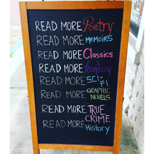 A sandwich board in front of Writer's Block Bookstore