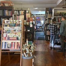 Inside Barner Books, featuring bookshelves and a rack of posters