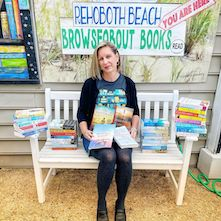 Susan from Browseabout Books in Rehoboth Beach, Delaware, with a stack of titles