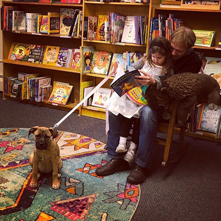 Father and daughter reading with dog at a bookstore