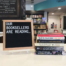 Our Booksellers Are Reading.... next to a stack of books