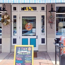 Exterior of Mitzi's Books showing the front door and a sandwich board