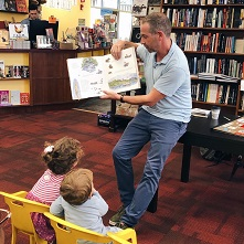 Man reading picture book to two children sitting in chairs