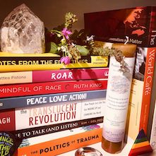 Stack of books with a crystal, dried flowers, and candle at Spiral Circle bookstore.