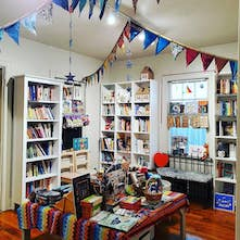 The inside of Spiral Circle Bookstore, including bunting hanging from the ceiling, a display table in the center of the room, and white bookshelves filled with books along the perimeter.