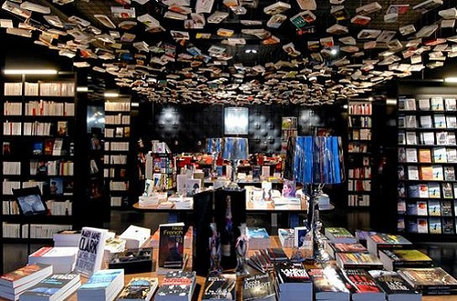 A neutral-colored bookstore that features merchandise on the shelves, and on the ceiling