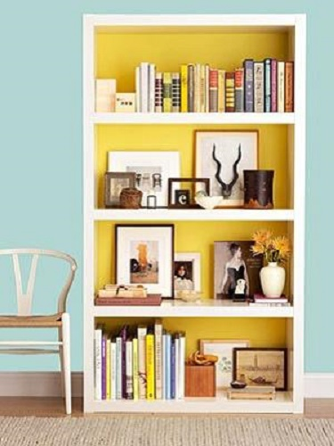 Painting the inside of a bookshelf can add a colorful accent to store fixtures