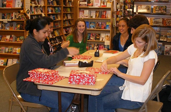 Volunteer wrappers help prepare books for charities through the Book Angel program at Anderson's.