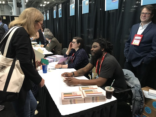 Indie Champion Jason Reynolds signs books in the ABA Member Lounge after the lunch.