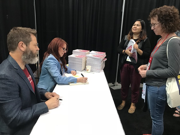 Nick Offerman and Megan Mullally sign books in the lounge.