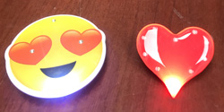 Yellow pin of smiley face with heart eyes, shiny red heart