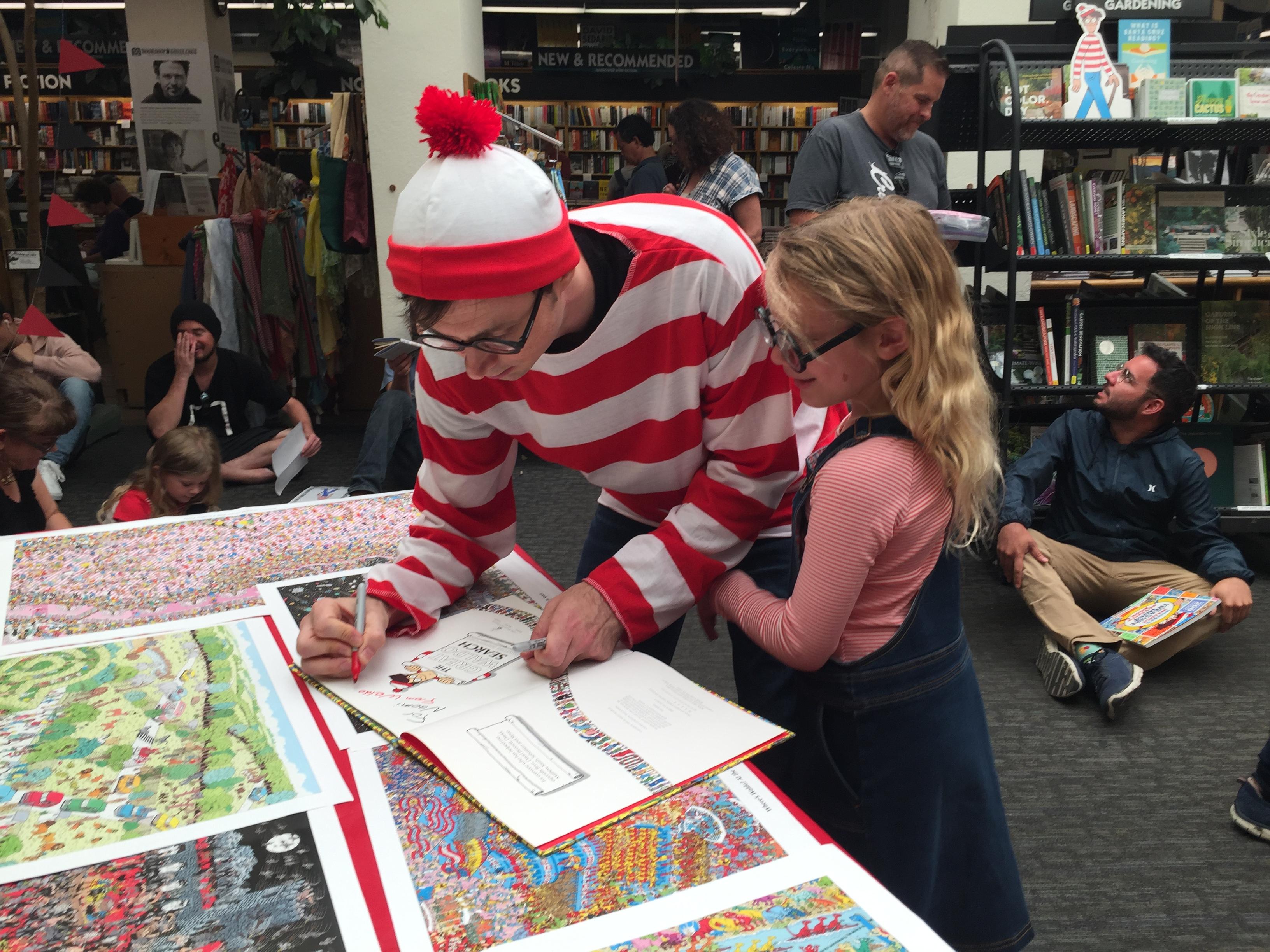 A staff member dressed as Waldo signs a participant's book at Bookshop Santa Cruz.