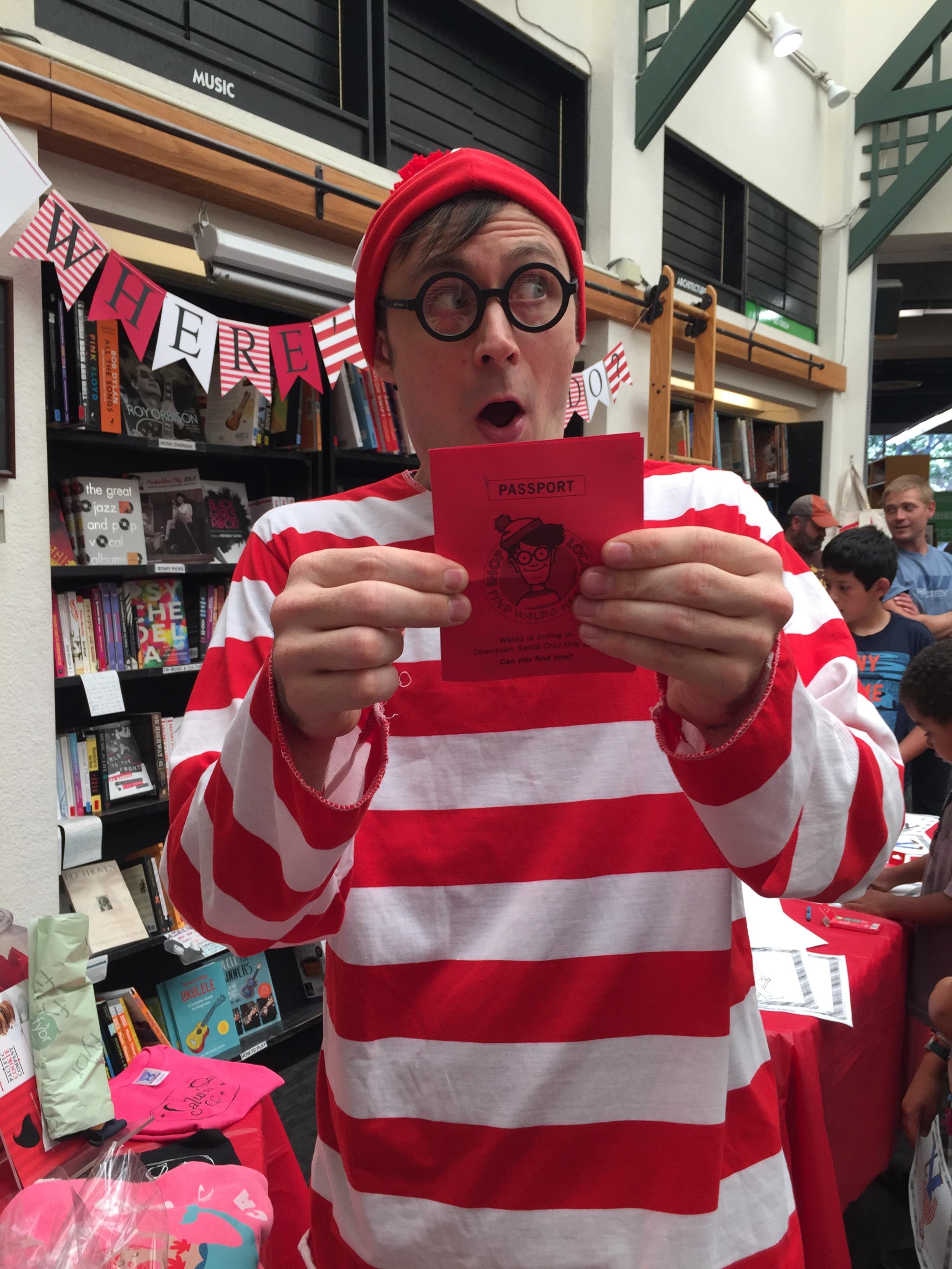 A staff member dressed as Waldo poses with a Find Waldo Local passport at Bookshop Santa Cruz.