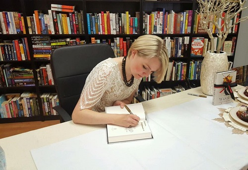 Partnering author Chelsea Bobulski signs books at Gathering Volumes