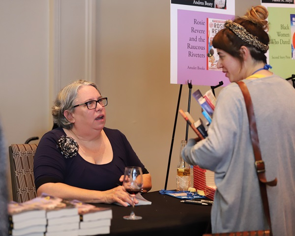 Andrea Beaty talks with a bookseller at the Author Reception.