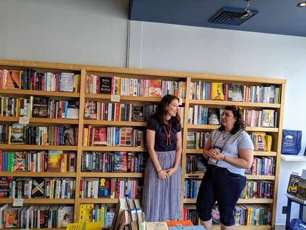 Jill Yeomans with a bookseller in front of a set of bookshelves at White Whale Bookstore