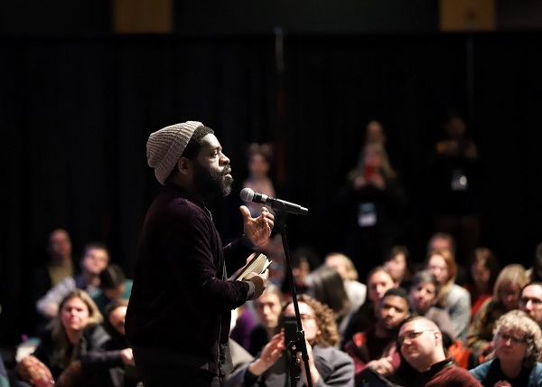 Hanif Abdurraqib addresses booksellers seated on the floor around him during his afternoon keynote.