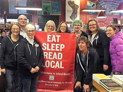 Staff of Island Books with a new Eat Sleep Read banner