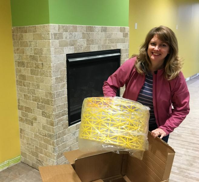 Liz Hopper Whitelam opens a box with a lampshade as she oversees renovation of her space in downtown Reading.