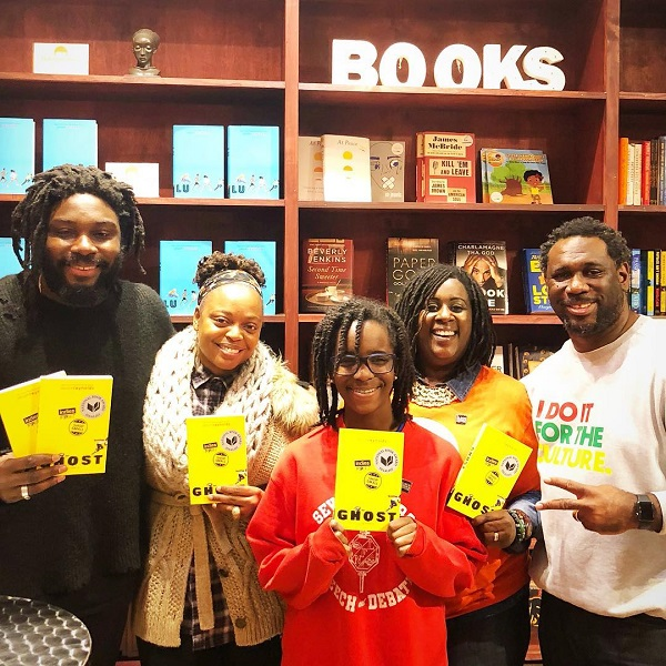 Readers pose with Jason Reynolds at MahoganyBooks.