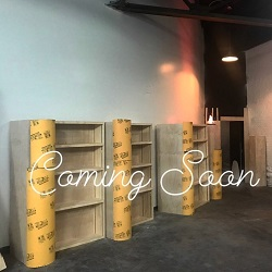 "An inside look at the new satellite location for Malaprop's. There are empty, unpainted shelves, and the words ""Coming Soon"" appear across the image."