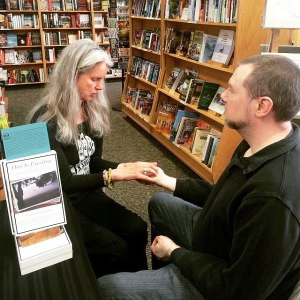 Odyssey Bookshop's Michael Downing gets his palm read by author Suzanne Strempek Shea.