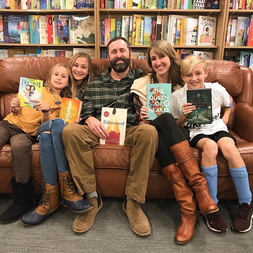 Author Kimmery Martin and her family posing with their favorite books at Park Road Books.