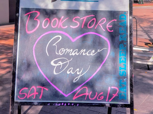 A sign promoting Bookstore Romance Day at Rediscovered Books.