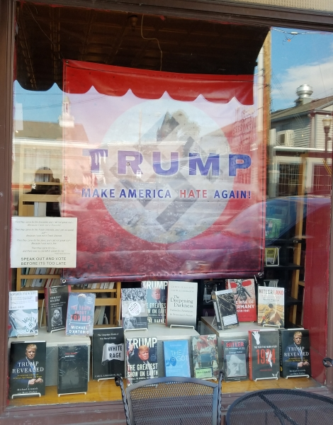 Anti-Trump banner in Inquiring Minds front window.