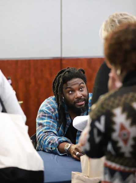 Jason Reynolds chats with booksellers at his author reception table.