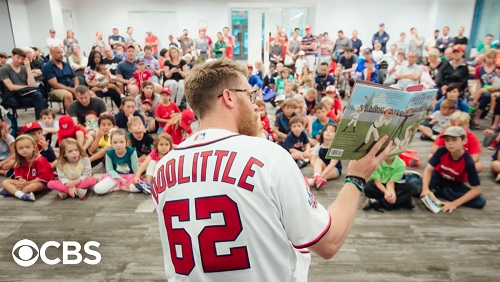 Sean Doolittle reading a picture book to a crowd of kids