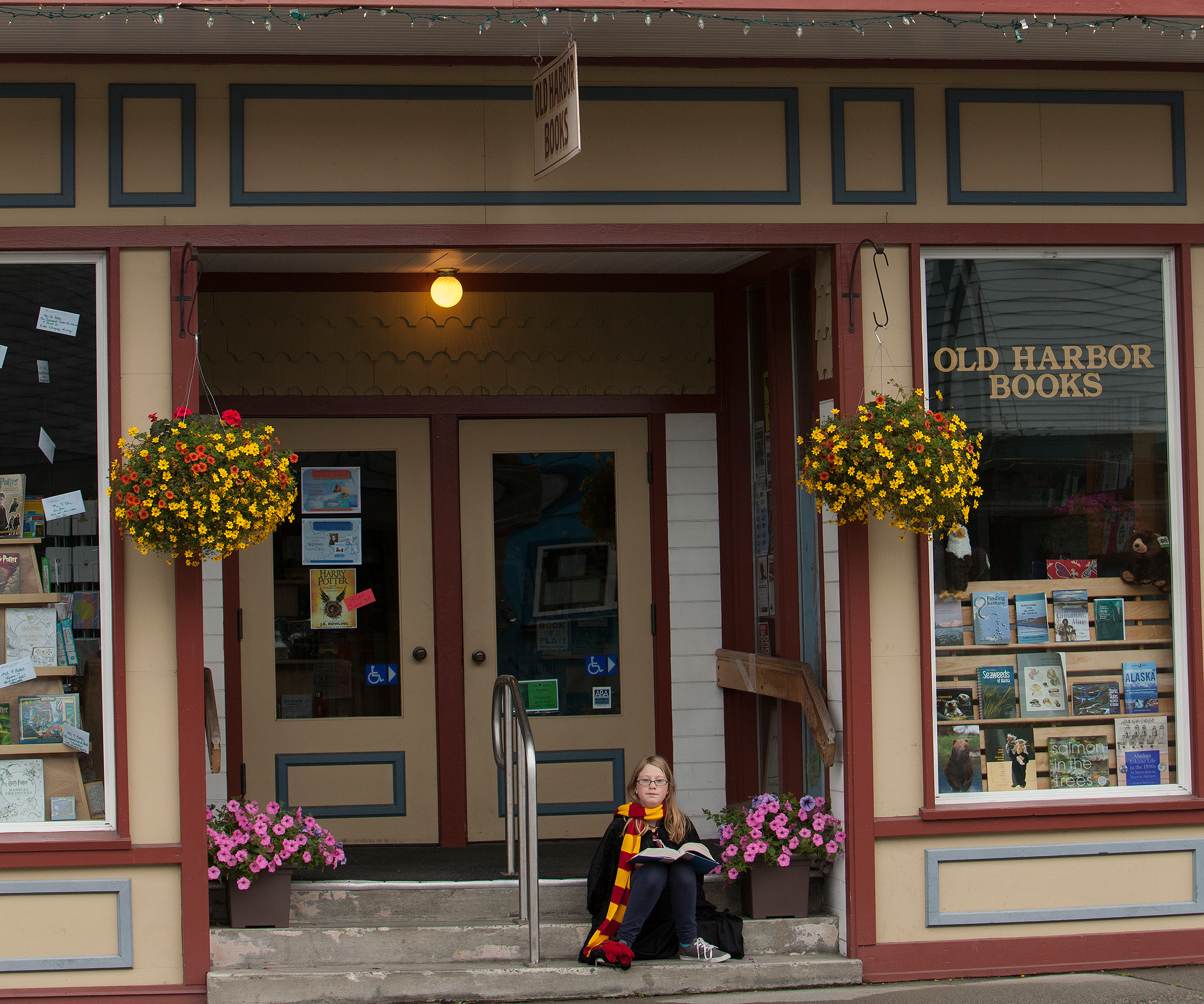 Old Harbor Books exterior with child in Hogwarts uniform on steps.