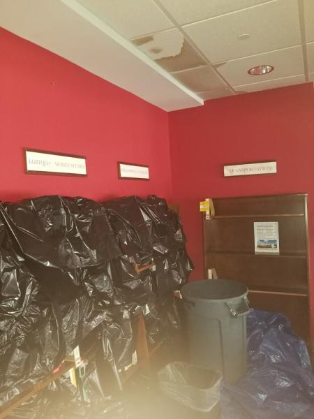 Staff at Quail Ridge covered book shelves with garbage bags during clean up.