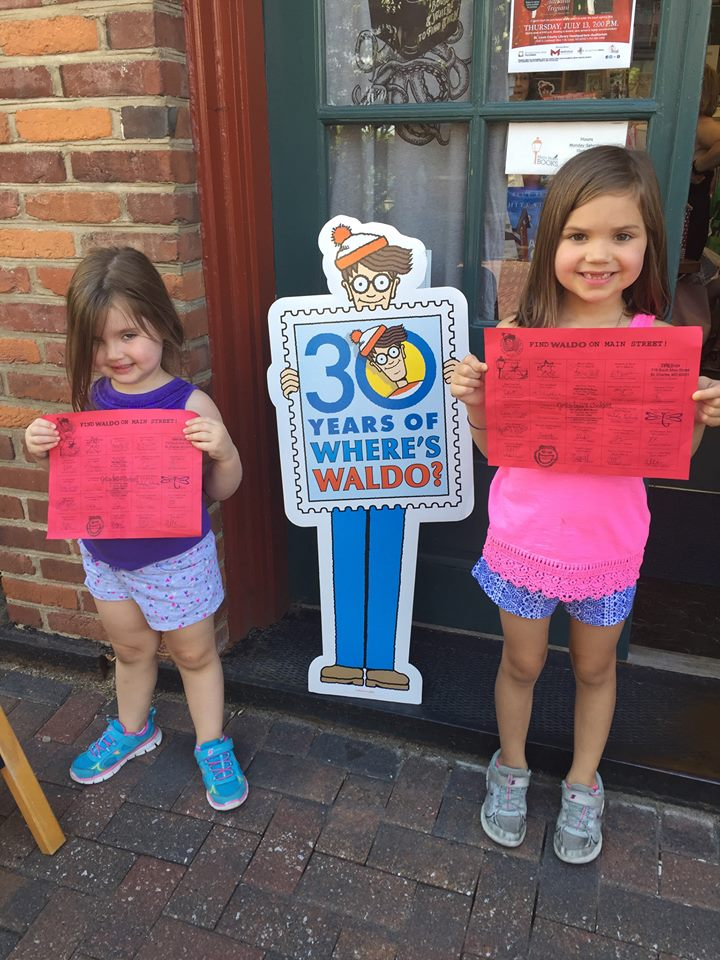 Children participating in Main Street Books' Waldo celebration hold up completed passports.